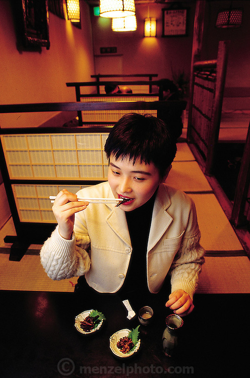 In a basement sushi bar in Tokyo, Japan, Mariko Urabe puts an inago, a grasshopper, between her teeth. She had never eaten one before this photograph and wasn't particularly interested in eating this one. As is true in many countries, food preferences are culturally based and don't necessarily extend to the entire country. (Man Eating Bugs page 37)