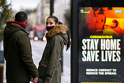 """© Licensed to London News Pictures. 12/01/2021. London, UK. A couple wearing a protective face coverings stand near the government's ''Stay Home, Save Lives' Covid-19 publicity campaign poster in north London, as the number of cases of the mutated variant of the SARS-Cov-2 virus continues to spread around the country. Prime Minister Boris Johnson has said that the public should """"stay at home"""". Photo credit: Dinendra Haria/LNP"""