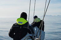 Sailers of bow of sailboat keeping watch for icebergs off east coast of Greenland