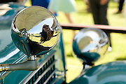 A guest uses the reflection of a headlight on a vintage car to apply her lipstick. L'Ormarins Queens Plate 2011. Image by Greg Beadle