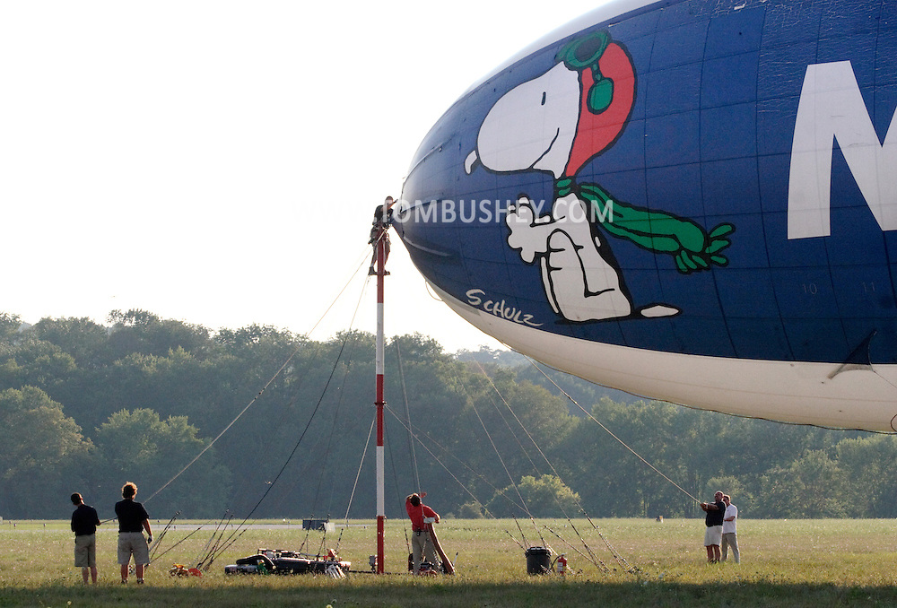 Montgomery, NY - Members of the ground crew control the MetLife blimp Snoopy Two as it is secured to the mooring mast at Orange County Airport on July 25, 2008.