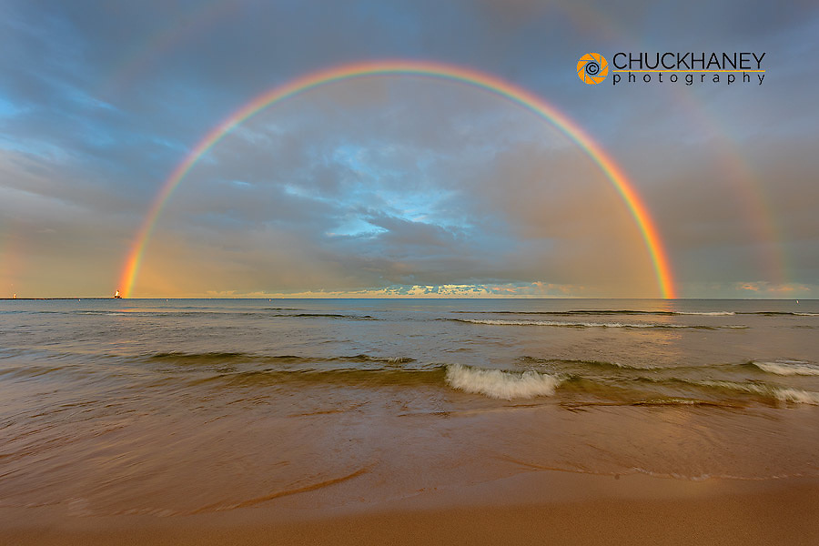 Full arcing rainbow over Lake Michigan and Ludington lighthouse in Ludington, Michigan, USA