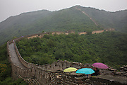 Tourists walk with umbrellas protecting themselves from the rain at The Great Wall of China.