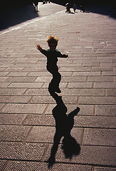 Europe, Italy, Sienna, boy waving in plaza, with shadow.  MR