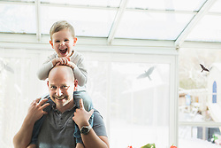 Portrait of father holding son on his shoulder