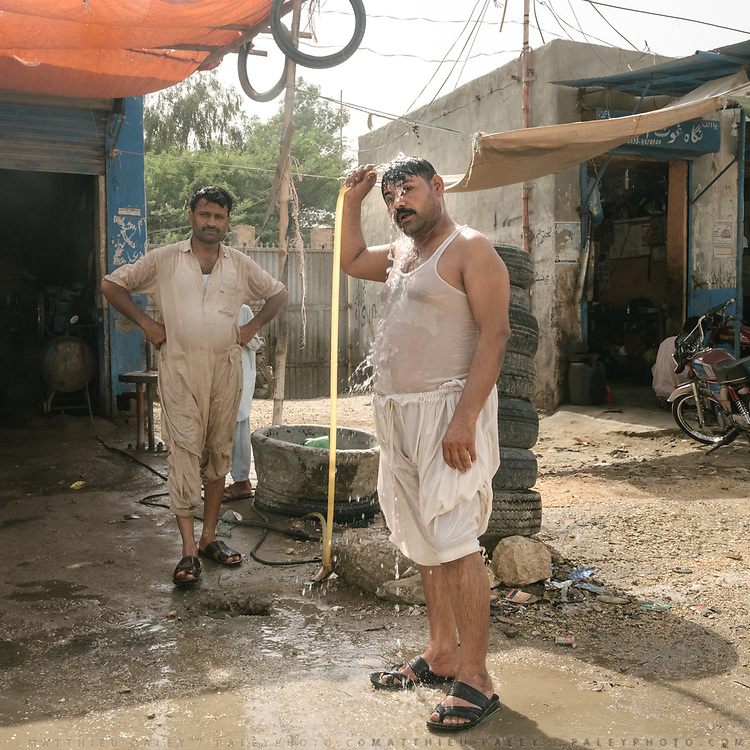 A car mechanic takes an impromptu shower in the middle of the day.