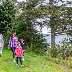 A couple walks with their two daughters on a trail at Quoddy Head State Park in Lubec, Maine.