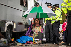 © Licensed to London News Pictures. 15/10/2019. London, UK. An Extinction Rebellion protester locked on to a caravan shelters beneath an umbrella, as demonstrators block Millbank with a caravan. Police have said that any Extinction Rebellion protesters who continue will be liable for arrest. Photo credit: Rob Pinney/LNP