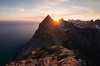 Midnight sun shines over mountains of Moskenesøy from Helvetestind, Lofoten Islands, Norway