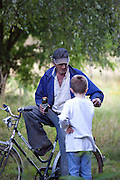 Polish farmer relaxing on his bicycle with a beer talking to neighboring young boy. Zawady Central Poland
