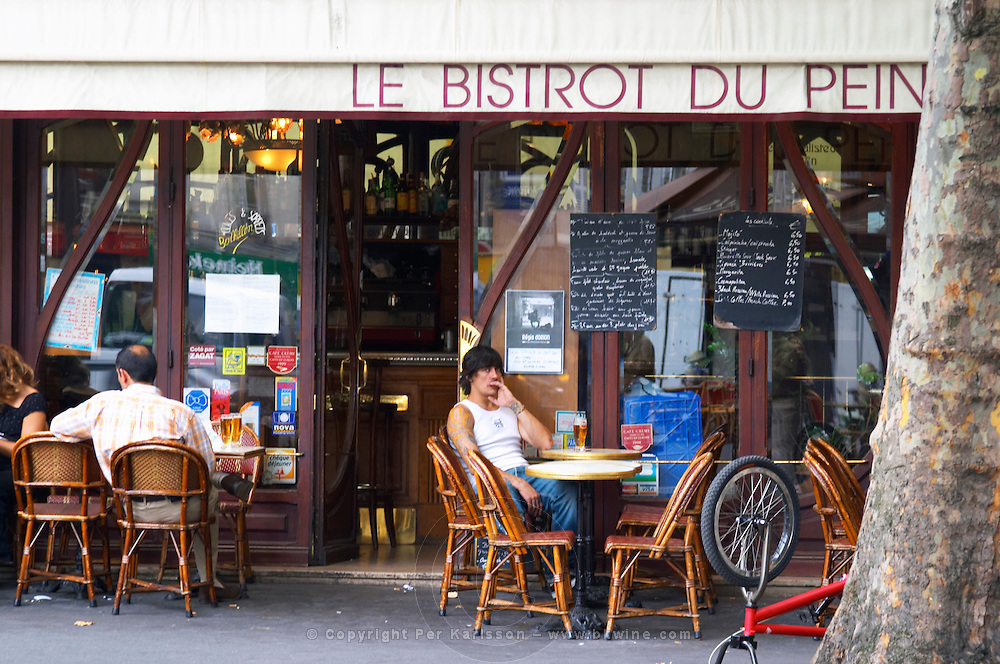 Le Bistrot du Peintre cafe bar terrase outside seating on the sidewalk. A young man sitting alone on a wicker chair at a table with a glass of beer The Bistrot du Peintre is an old fashioned Paris café cafe bar restaurant of art nouveau design with polished brass, mirrors and old signs