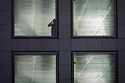 A person speaks on a handheld device at the window of a vacant office building in the City of London.