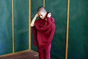 A young novice monk prepares his robes ready to collect alms at a temple in Insein on 17th May 2016 in Yangon, Myanmar