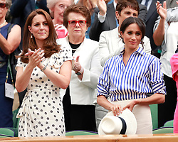 The Duchess of Cambridge and The Duchess of Sussex applaud after watching Novak Djokovic beat Rafael Nadal in the royal box on centre court on day twelve of the Wimbledon Championships at the All England Lawn Tennis and Croquet Club, Wimbledon.