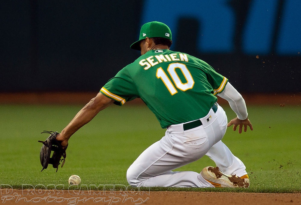 Jul 25, 2019; Oakland, CA, USA; Oakland Athletics shortstop Marcus Semien (10) can't make the sliding stop of a ground ball by Texas Rangers Asdrubal Cabrera during the fifth inning of a baseball game at Oakland Coliseum. Cabrera was safe at first. Mandatory Credit: D. Ross Cameron-USA TODAY Sports