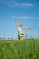 Girl (10-11) jumping in field, smiling