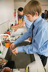 Secondary school students washing paint brushes at the end of an art lesson,