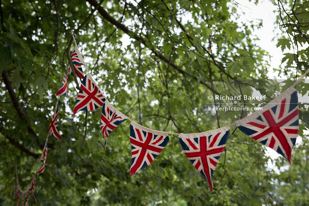Union Jack bunting hangs in the trees of a London park, on 24th June 2017, in Ruskin Park, the south London borough of Lambeth, England. Bunting is a festive decoration made of fabric, or of plastic, paper or even cardboard in imitation of fabric. Typical forms of bunting are strings of colorful triangular flags and lengths of fabric in the colors of national flags gathered and draped into swags or pleated into fan shapes. The term is also used to refer to a collection of flags, and particularly those of a ship. The officer responsible for raising signals using flags is known as bunts, a term still used for a ship's communications officer.