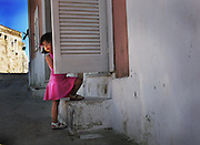 A young girl in a pink dress peeks out from behind a door into her home in Ponza, Italy