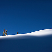 A streak of morning light creates a wave of white against blue shadows and sky. Big Cottonwood Canyon, Utah