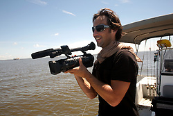 21 August 2010. Barataria Bay, south Louisiana. <br /> Intrepid french news reporter Arnaud Muller of France 2 TV's version of 60 minutes reports on the BP oil spill.<br /> Photo credit; Charlie Varley/varleypix.com