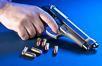 Hand holding a gun and bullets in blue background.