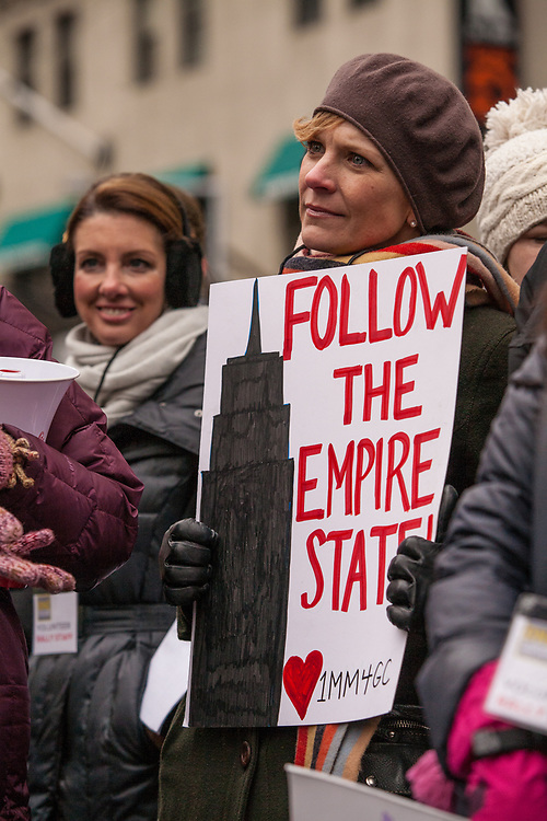 "A woman bears a sign reading ""Follow the Empire State."" New York was the first state to pass new gun laws after the shootings in Newtown, Connecticut."