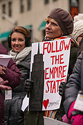 """A woman bears a sign reading """"Follow the Empire State."""" New York was the first state to pass new gun laws after the shootings in Newtown, Connecticut."""