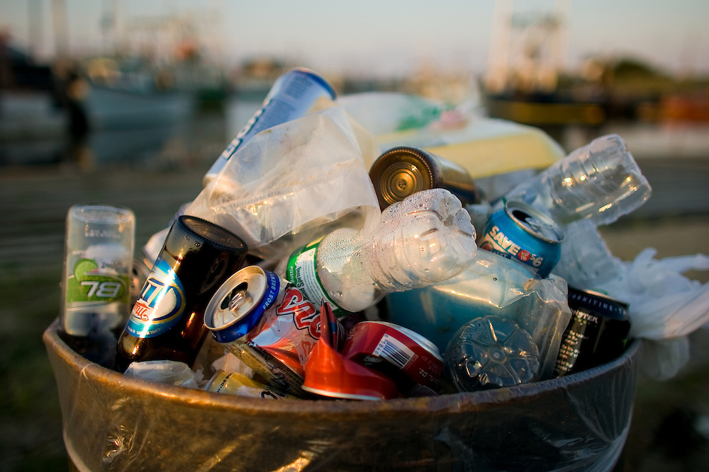 A overflowing trash can will with all sorts of rubbish including beer can, beer bottles, plastic water bottles,  aluminum cans.  The area part of a township owned waterfront park had litter everywhere.