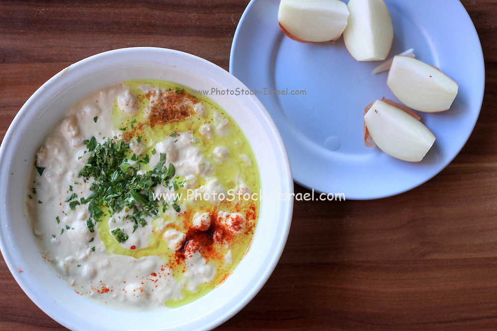 Hummus. A Levantine Arab dip or spread made from cooked, mashed chickpeas, blended with tahini, olive oil, lemon juice, salt and garlic.Served with fresh onions