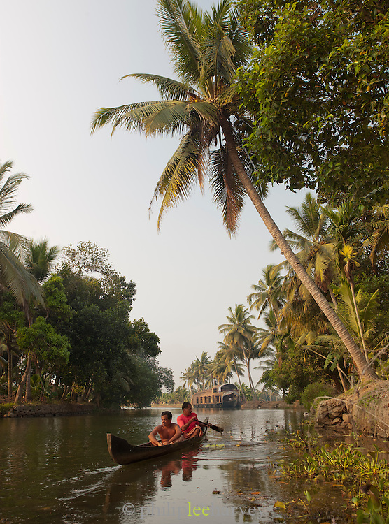 Men paddling in their canoe in the Kerala Backwaters, near Alappuzha, India