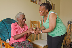 Carer giving elderly visually impaired woman a cup of tea
