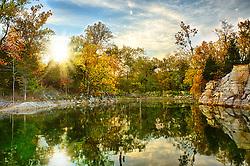 The sun rises behind the trees near the cove at Klondike Park lake