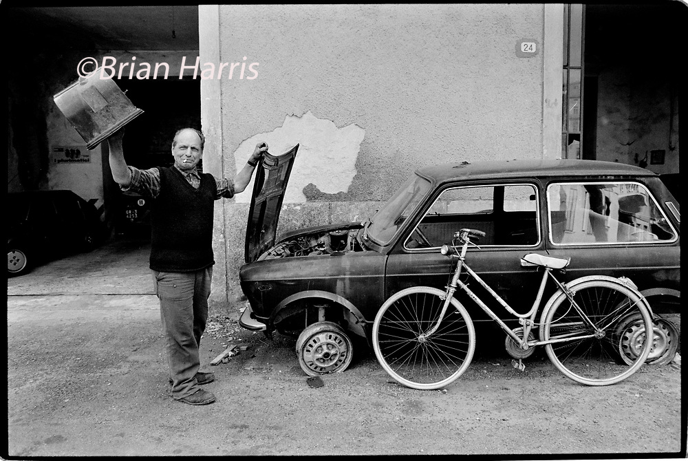 Casole d'Elsa, Tuscany, Italy. 1990. Scanned in 2019<br /> Street and cafe bar life in the small hill top town of Casole d'Elsa in Tuscany Italy. Man with car neading some attention.