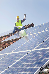 Engineer making peace gesture while taking break from installing solar panels on house roof