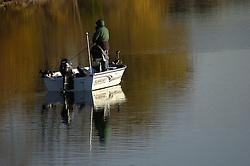 Man fishing in a motorized fishing boat on a lake