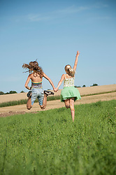 Two carefree happy young girls running field