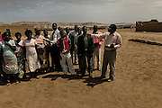 Tchikuteny with some of his sons and daughters after leaving the church. In Angola?s Namibe desert, at Giraul, in the Namibe province, Tchikuteny, from the Mucubal tribe, is the leader of a big family, maybe the biggest family in the world.<br /> He is the chief leader, the manager and responsible for the entire village. <br /> In his village, Tchikuteny lives nowadays with most of his big family, his 33 wives, that were once 43, but 10 left the village, and most of their descendants.<br /> Tchikuteny maintains the registry of all the new-borns, totalizing 154 sons, and his grandsons, that are around 60. Nowadays, 4 new babies are on the way, and 3 great grand children were born recently.<br /> Huge harmony, love and respect transpire in the village atmosphere. The sense of a community is the pillar of their sustainability and sustenance and their autonomy depends prominently on cattle and agriculture that is made by the villagers. Nevertheless, Tchikuteny village is in close connection with their surrounding communities. Children attend Giraul School and there is proximity and relations with the extended family that lives in the surroundings.<br /> Being the spiritual leader of the community, Tchikuteny is also responsible for the weekly religious works that happens in the village church. <br /> This big family opened his doors to share with us their daily lives.