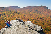 From atop Hanging Rock, view across a sea of autumn orange and red foliage to Moore's Wall, at Hanging Rock State Park in Stokes County, North Carolina, USA. (Panorama stitched from 2 images.) The eroded quartzite knob called Hanging Rock rises to 2150 feet elevation. The park is 30 miles (48 km) north of Winston-Salem, and approximately 2 miles (3.2 km) from Danbury. Hanging Rock State Park is located in the Sauratown Mountain Range, which is made up of monadnocks (or inselbergs, isolated hills) that are separated from the nearby Blue Ridge Mountains. Prominent peaks in the Sauratown range rise from 1,700 feet (520 m) to more than 2,500 feet (760 m) in elevation and stand in contrast to the surrounding countryside, which averages only 800 feet (240 m) in elevation. Named for the Saura Native Americans who were early inhabitants of the region, the Sauratown Mountains are the erosion-resistant quartzite remnants of mountains pushed up between 250 and 500 million years ago.