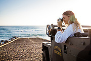 Woman sat in her landrover on the slipway at St Ouen's Bay, Jersey, CI, taking photos of the surf and sea in low sunlight.