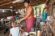 Apr. 3, 2010 - KHUN SAMUTCHINE, THAILAND: A man talks to his son in front of their home in Khun Samutchine. Rising sea levels brought about by global climate change threaten the future of Khun Samutchine, a tiny fishing village about 90 minutes from Bangkok on the Gulf of Siam. The coastline advances inland here by about 20 metres (65 feet) per year causing families to move and threatening the viability of the village. The only structure in the village that hasn't moved, their Buddhist temple, is completely surrounded by water and more than 2 kilometers from the village. The temple and the village have asked the Thai government and several NGOs for help, but the only help so far is a narrow concrete causeway the government is building that will allow people to walk into the temple from a boat landing two miles away. The walk to the village from a closer boat landing is shorter, but over an unimproved mud flat that is nearly impassible in the rainy season.  PHOTO BY JACK KURTZ