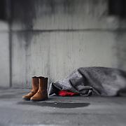 Homeless man sleeping under bridge