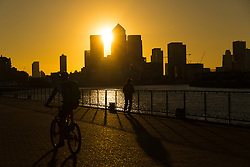 © Licensed to London News Pictures. 05/10/2016. LONDON, UK.  People walk on the River Thames path as the sun rises behind Canary Wharf and London's financial district this morning. Forecasters are predicting a day of clear and sunny weather in London today.  Photo credit: Vickie Flores/LNP