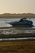 Anchored boat stuck in tidal mud flat at low tide in Morro Bay, California