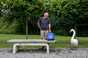 A Mute Swan eyes up the lunch being hidden by a nervous visitor to a rural central Slovenian town, on 25th June 2018, in Spilje, Slovenia.