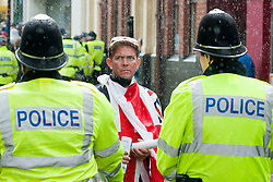 An EDL supporter wapped in the Union Flag looks back past police officers as they escort<br /> EDL members and supporters towards Rotherham Minster during Saturdays EDL rally in South Yorkshire in Rotherham Town Centre <br /> May 10 2014<br /> Image © Paul David Drabble <br /> www.pauldaviddrabble.co.uk