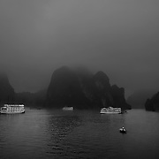 A local seller rows to tourist boats, surrounded by early morning mist, to sell her goods in Ha Long Bay, Vietnam. The bay consists of a dense cluster of 1,969 limestone monolithic islands. Ha Long Bay, is a UNESCO World Heritage Site, and a popular tourist destination. Ha Long, Bay, Vietnam. 11th March 2012. Photo Tim Clayton
