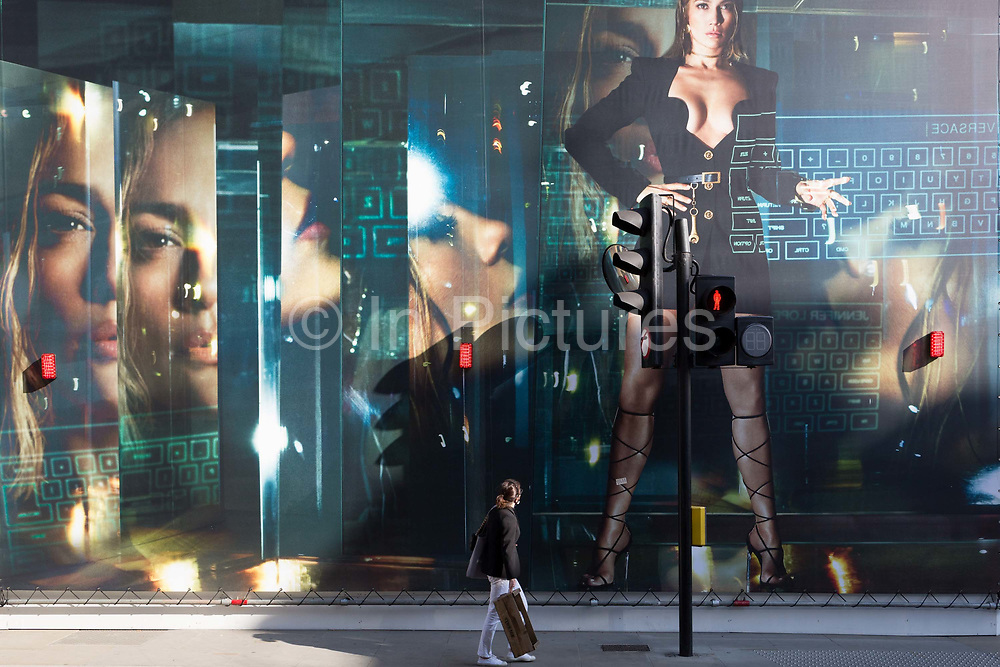 With a further 184 reported UK Covid deaths in the last 24 hrs, a total now of 43,414, a lady looks at a billboard during the construction of a new Versace store on New Bond Street during the Covid pandemic lockdown, now easing after three months of the Stay At Home policy but now being relaxed as the shops re-open, on 26th June 2020, in London, England. Government restrictions on the 2 metre rule is to be realxed on 4th July and replaced with one metre plus in the hope it stimulates the struggling UK economy.