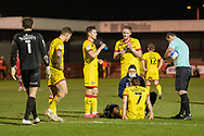 Walsall players take a break as Walsall midfielder Stuart Sinclair (#7) recives treament during the EFL Sky Bet League 2 match between Crawley Town and Walsall at The People's Pension Stadium, Crawley, England on 16 March 2021.