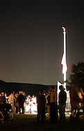 Washingtonville, N.Y. - Beams from the Tribute in Light in Manhattan are visible in the background at the Washingtonville 5 Firefighters World Trade Center Memorial after a candleight service on Sept. 11, 2006. The Memorial was built in honor of five FDNY firefighters from Washingtonville and the many others who lost their lives on September 11, 2001 in the World Trade Center terrorist attack.